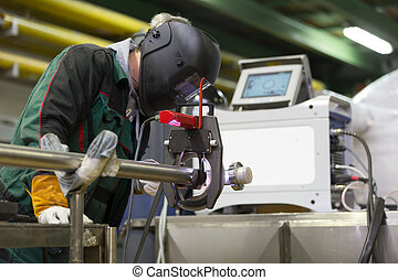 Industrial worker setting orbital welding machine -...