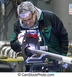 Industrial worker setting orbital welding machine. -...