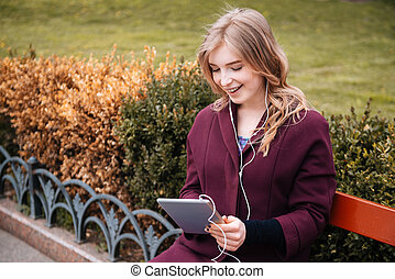 Woman sitting on bench and listening to music from tablet -...