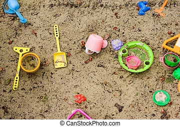 toys in a sandbox - picture of color plastic toys in humid...