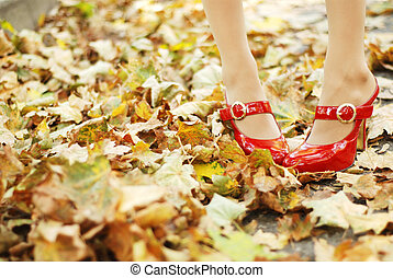 foliage and red shoes - woman's legs in a red patent-leather...