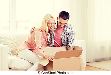 happy couple with cardboard box or parcel at home - people,...