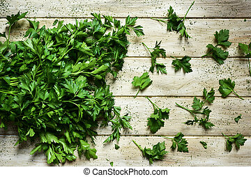 buncho of parsley on a rustic white table - high-angle shot...