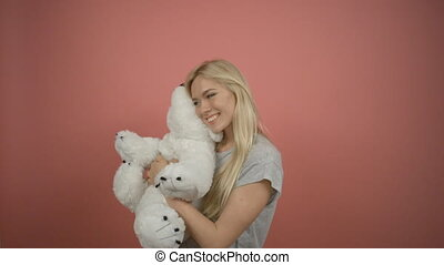 Beautiful blonde woman posing in the studio hugging a teddy bear