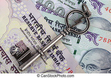 Old metallic key on Indian rupees