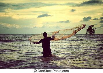 retro look image of a man throwing fishing net with sunset...