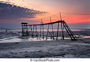 Beautiful structure at low tide with magical color sunset background of Jeram beach, Malaysia in long exposure