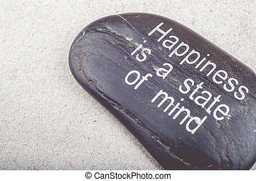"""Zen picture of """"Happiness is a state of Mind"""" message engraved on a stone in the sand"""