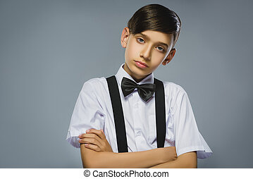 Portrait of calm and mistrust boy isolated on gray...