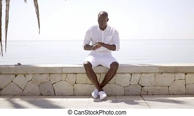 Handsome black model wearing shorts and shirt while seated...