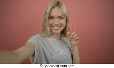 Smiling young blonde woman making selfie photo with peace...
