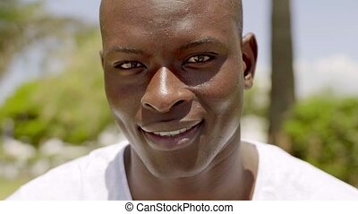 Close up of smiling handsome bald black man with a clear...