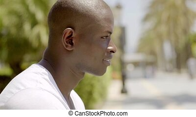 Close up side view of handsome bald black man in white shirt...