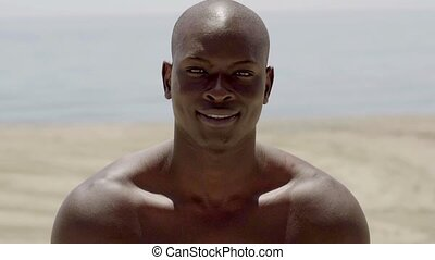 Close up of handsome shirtless black man staring at camera...