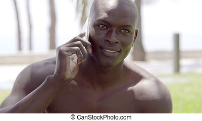 Bald black man speaking on phone in the park as sun...