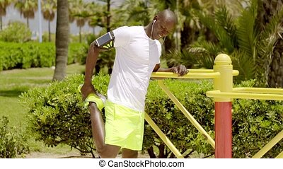 Bald black man in bright green shorts and ear buds listening...