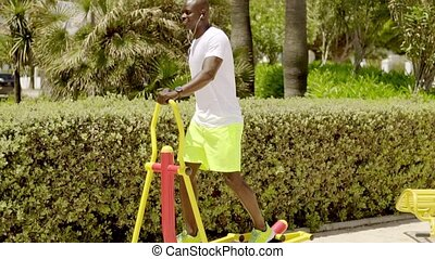 Man in park uses painted metal exercise equipment in the...