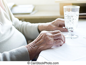 Senior womans hands with glass of water - Close up of old...