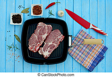 Two pieces of pork meat in a pan and spices for cooking in...