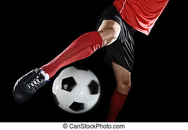 close up legs and soccer shoe of football player in action kicking ball isolated on black background