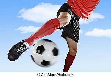 close up legs and soccer shoe of football player in action outdoors kicking ball isolated on blue sky