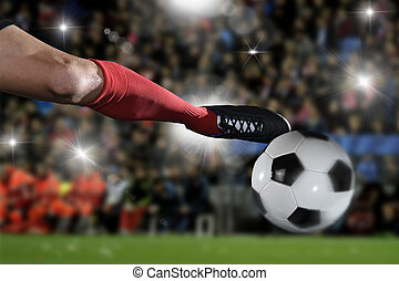 close up legs and soccer shoe of football player in action kicking ball playing in stadium