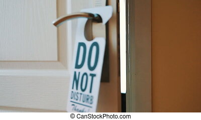 Swinging Do No Disturb sign at hotel room door