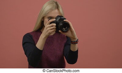 Glamour blonde woman photographer holding a digital camera...