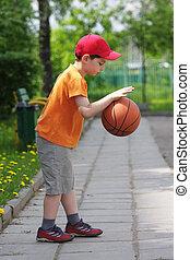 Little boy dribbling basketball sideview - Little boy in...