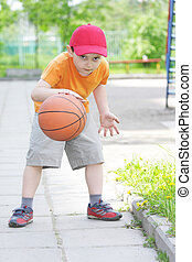 Little boy dribbling basketball - Little boy in orange shirt...