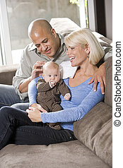 Loving parents with baby sitting on lap at home