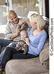 Parents and baby on lap at home, dad with camera