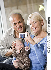 Parents with baby at home, mom holding camera