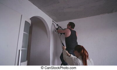 Man and Woman Making Renovated Apartment - Woman and man...
