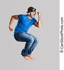 Young man jumping and listening music isolated over a gray...