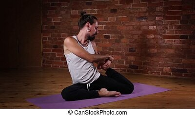 Man doing yoga exercise indoors - Young Caucasian man doing...