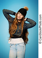 funny hat - Happy teenager girl in jeans and sweater smiling...
