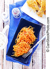 salad from carrot on black plate and on a table