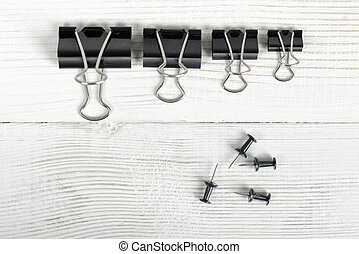 Black binder clips posted from biggest to the smallest on a...
