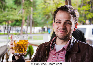 Man drinking beer outdoors in a cafe with funny expressions