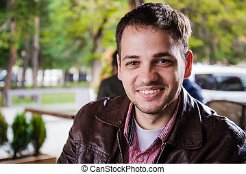 Young adult handsome man sitting at cafe or street restaurant and smiling