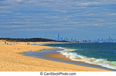 Atlantic Ocean shore at Sandy Hook with view of NYC. Sandy...