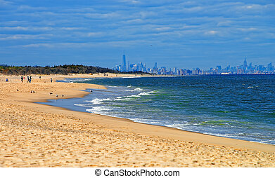 Atlantic Ocean shore at Sandy Hook with view on NYC. Sandy...