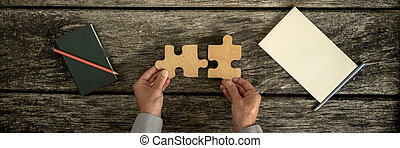 Top view of male hands assembling two wooden puzzle pieces...