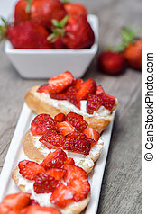 Strawberry sandwiches with cream cheese on white plate
