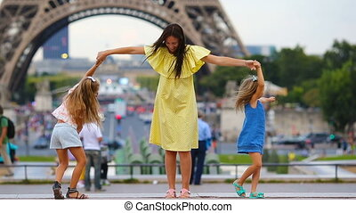 Happy family in Paris near Eiffel tower. French summer...