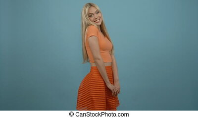 Beauty fashion portrait of blonde woman wearing orange skirt...