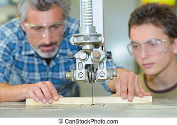 Student observing teacher sawing wood