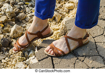 wary step on a stony road Closeup woman legs