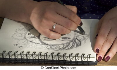 Closeup of a womans hand painting with graphite
